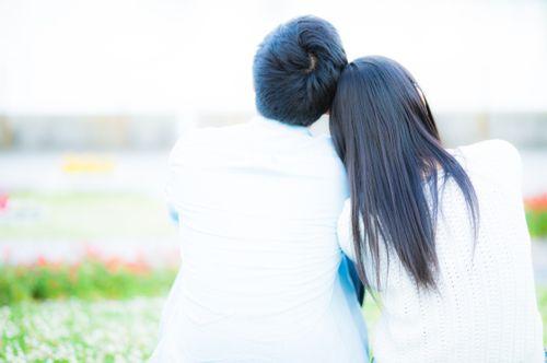 肩を寄せる男女の後ろ姿の写真