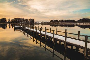 夕焼けに染まる湖面と桟橋の写真