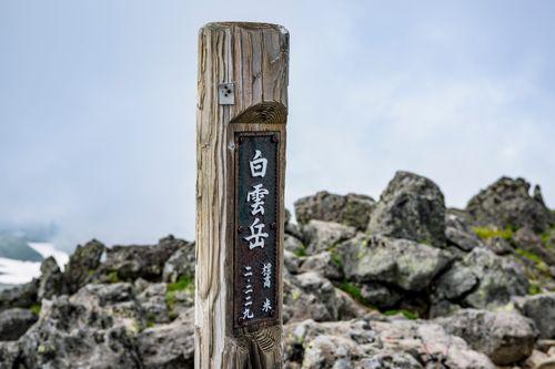 背景に雲が目立つ大雪山白雲岳の木碑の写真
