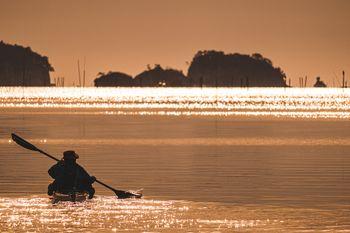 朝日の中を漕ぎ出すカヌーのシルエットの写真