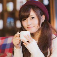 満面の笑みでコーヒーを飲む彼女の写真