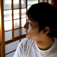 和室から外を見つめる男性の写真