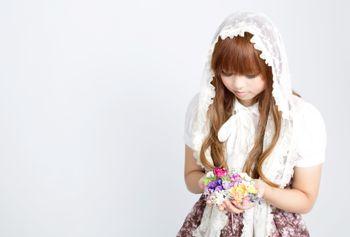 花のアクセサリーを両手いっぱいに持つゆるふわな女の子の写真