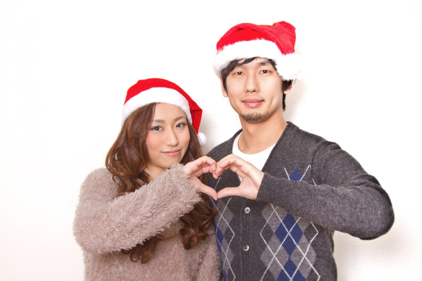 クリスマスに指でハートの形を作る恋人の写真
