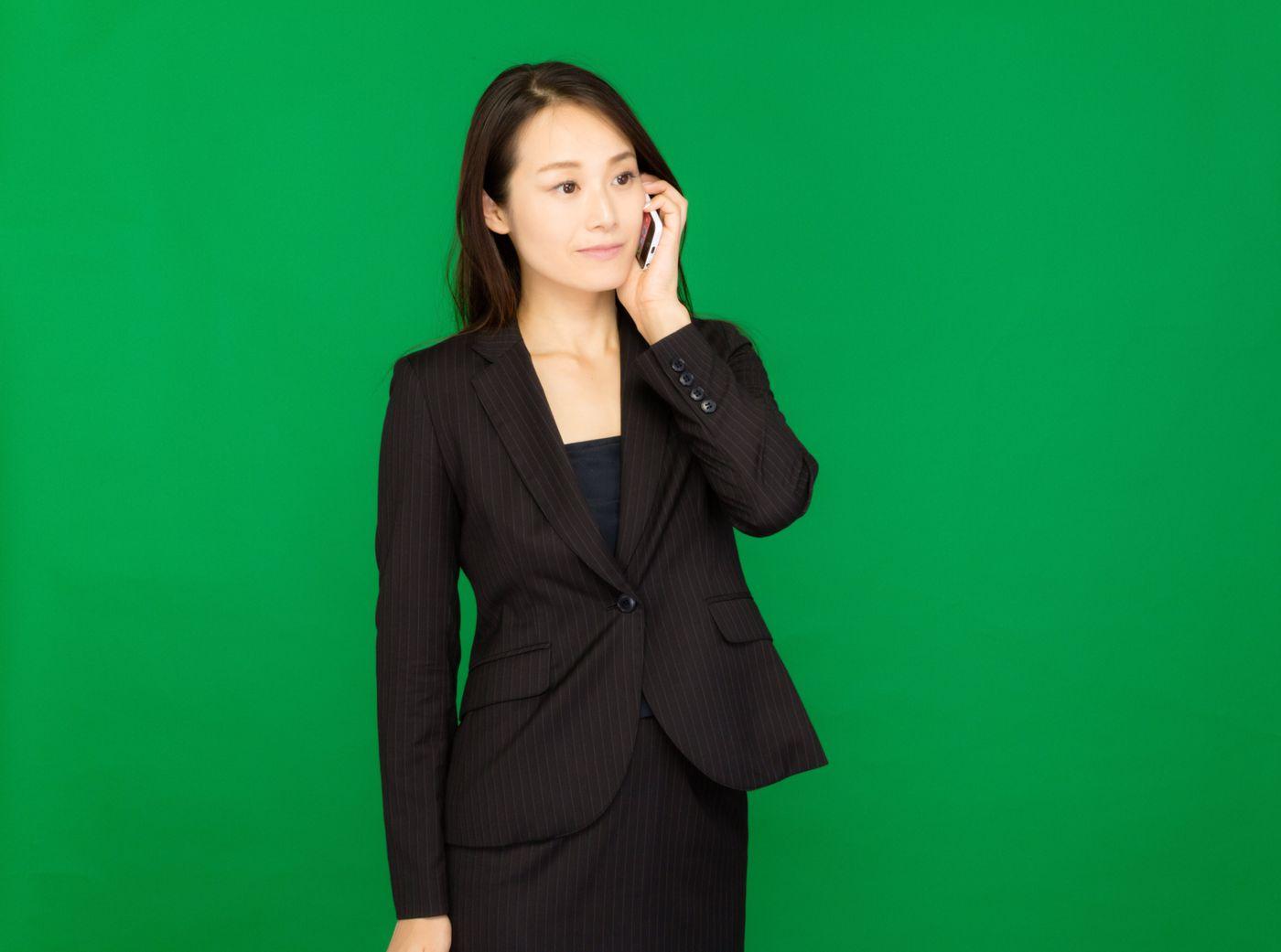 電話で社長に確認するキャリアウーマン(グリーンバック)の写真