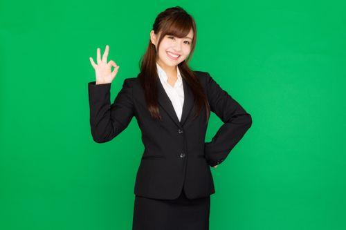 バッチリOK!と手で合図を送るスーツ姿の若い女性(グリーンバック)の写真