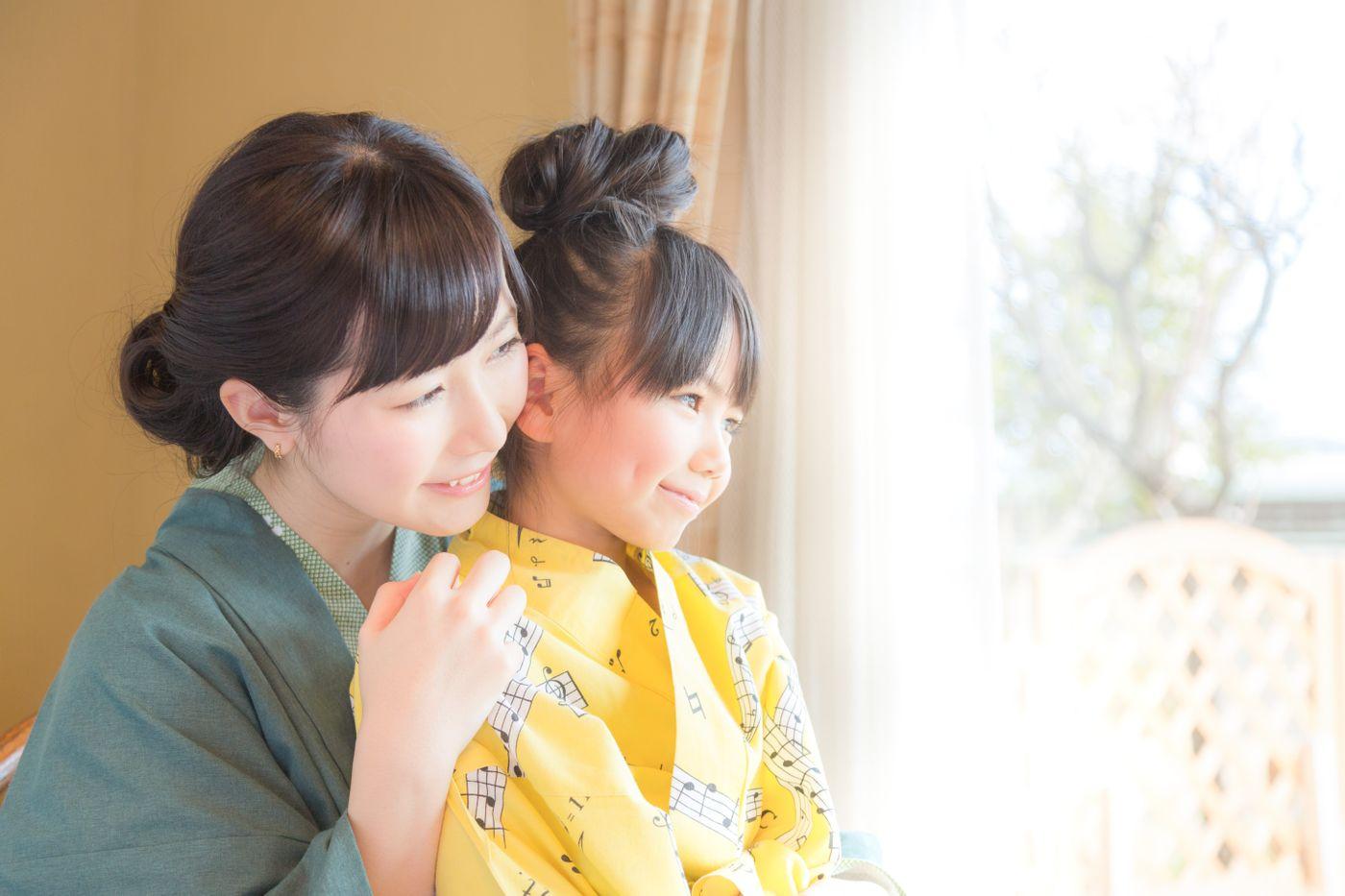 温泉旅館の客室から庭先を眺める親子の写真
