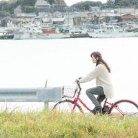 自転車で買い物に出かける女性の写真