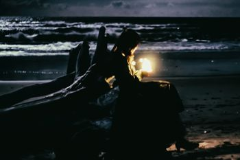 流木と暗闇を照らす灯りの写真