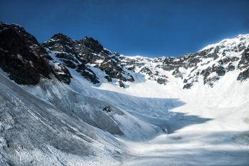 涸沢に伸びる影と残雪期の吊尾根(北アルプス)の写真
