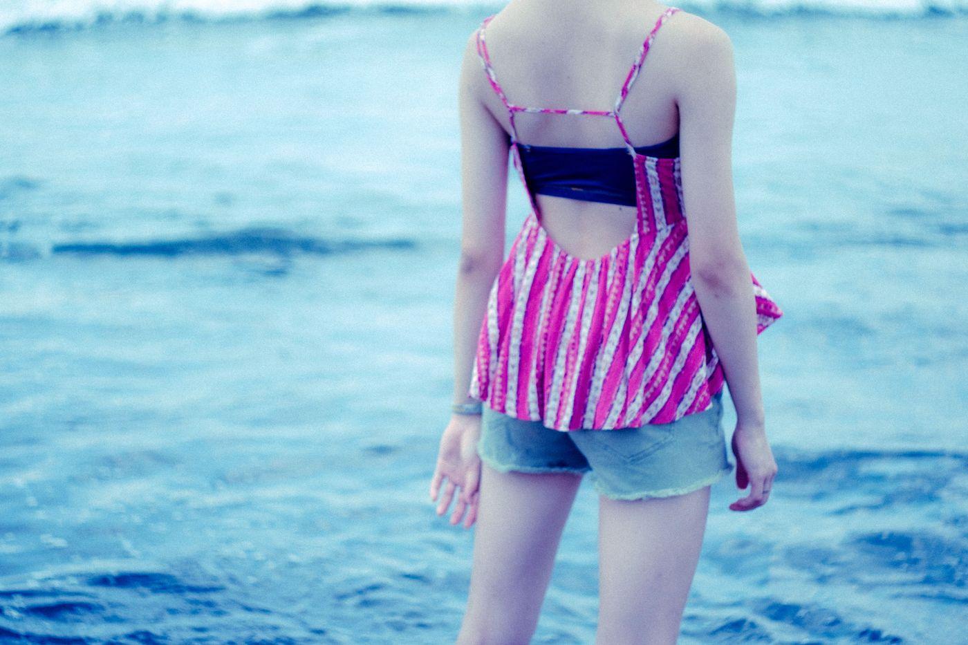 波打ち際に立ちすくむ若い女性の後ろ姿(夏)の写真