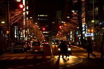 夜、大通りの横断歩道を渡る人の写真