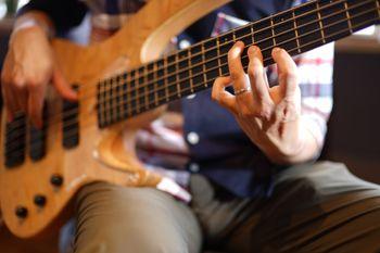 5弦ベースを弾くベーシストの左手フォームの写真