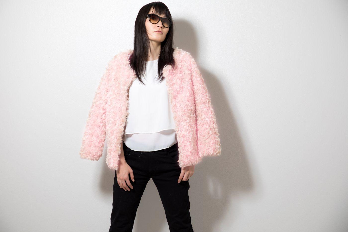 ピンク色のプードルコートを着た女性の写真
