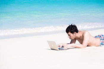 宮古島の前浜ビーチで急な修正依頼に対応するバカンス中のプログラマーの写真