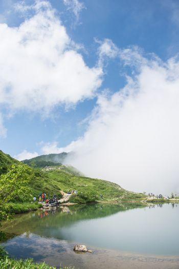 湖面に映る雲と登山者の写真