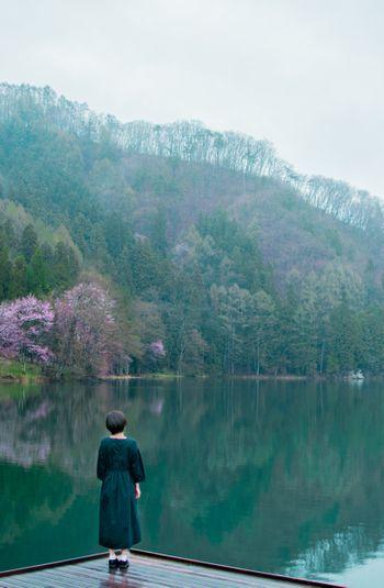 水鏡の湖畔に佇む後ろ姿の女性の写真