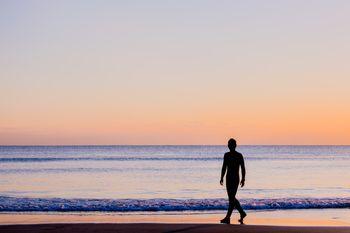 夕暮れの砂浜を歩く男性のシルエットの写真