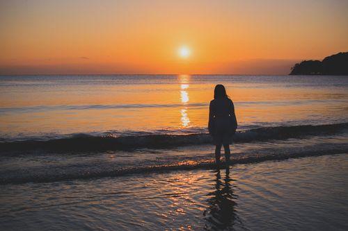 夕日に向かって浜辺に立ちすくむ女性の写真