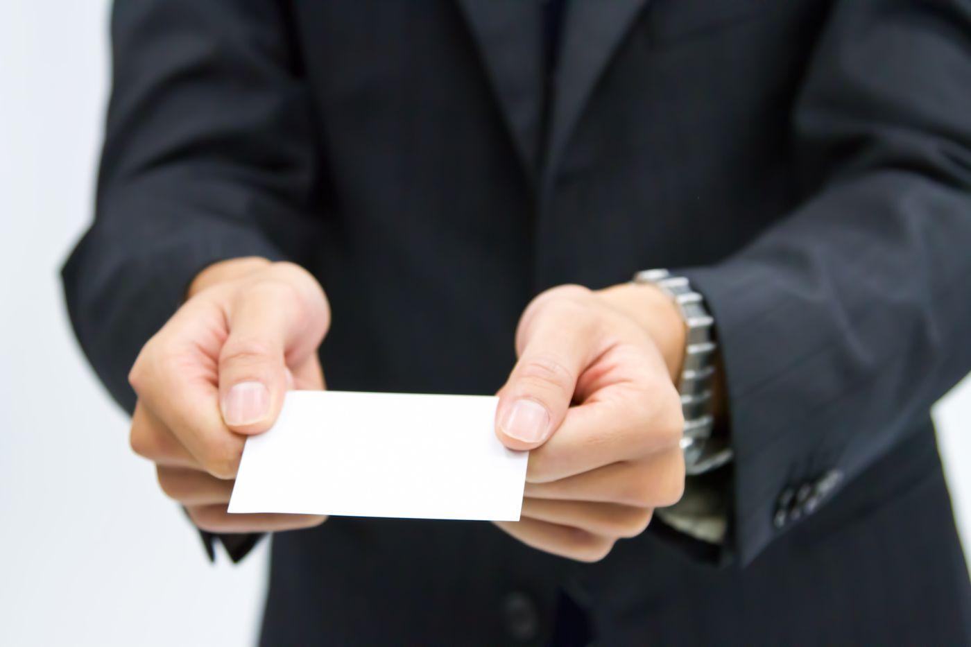 両手で名刺を渡すビジネスマンの写真