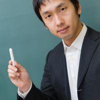 チョークを持つスーツ姿の先生の写真