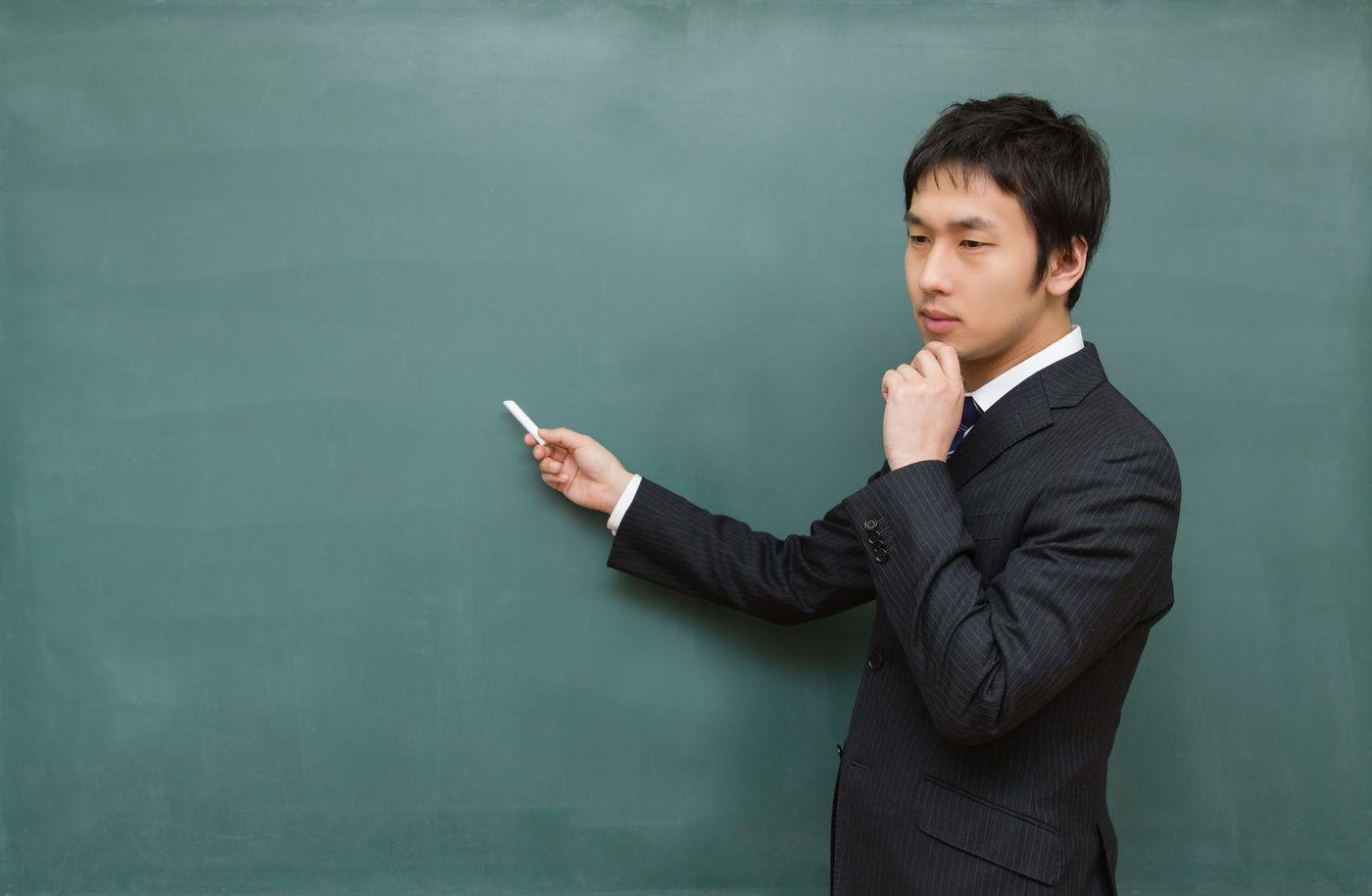 黒板に向かって考えてしまう先生の写真