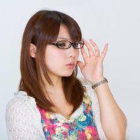 メガネを直す女性の写真