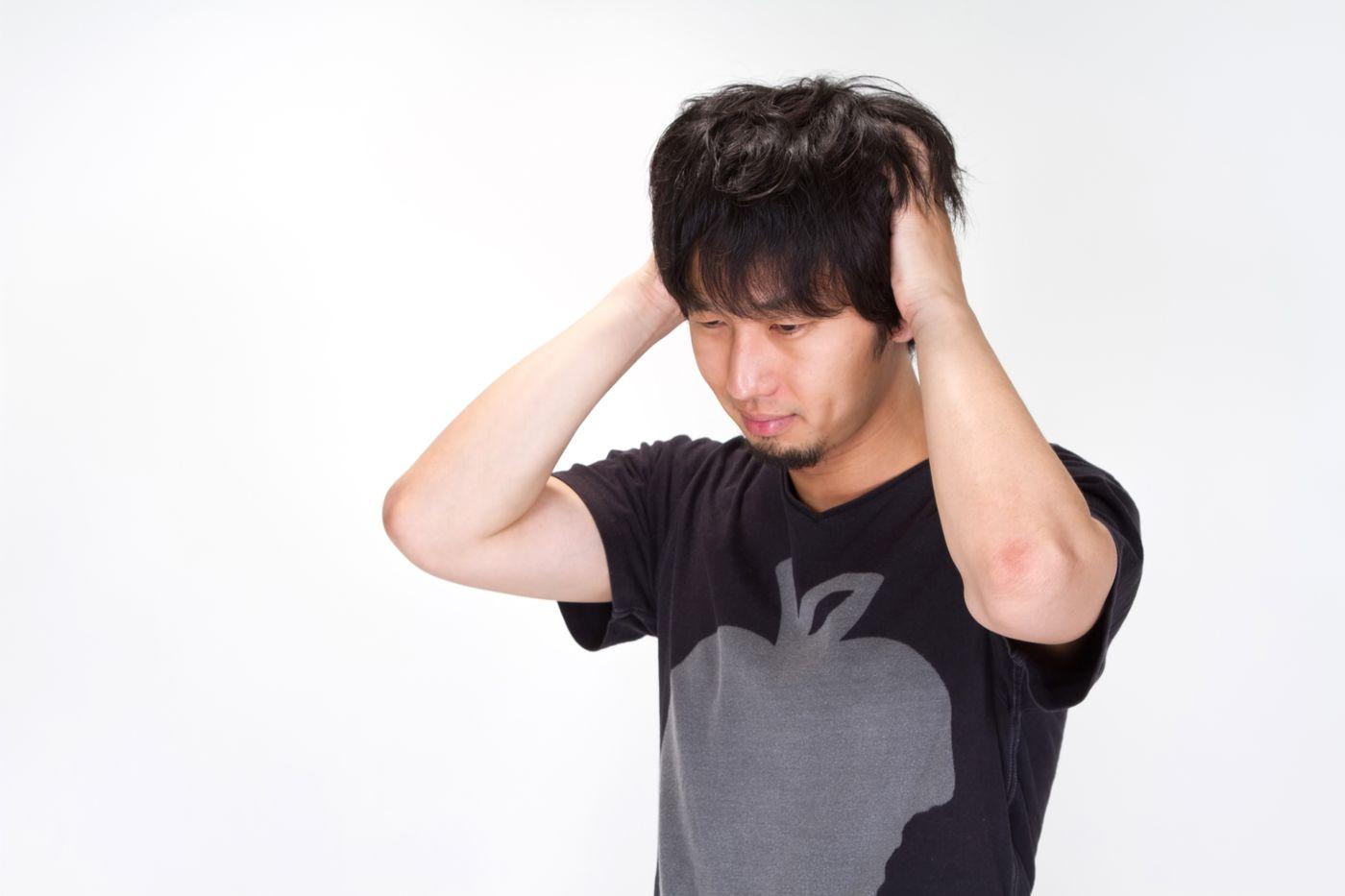 悩み、頭をかきむしる男性の写真