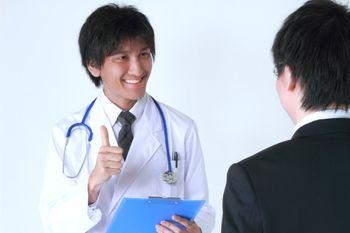 サラリーマンに笑顔で診断結果を話す医者の写真