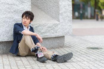 膝を立てて座る青年の写真