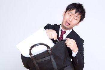 縦なら入るとファスナーを閉めようとするビジネスマンの写真