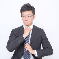 ネクタイを締め直す眼鏡をかけたビジネスマンの写真