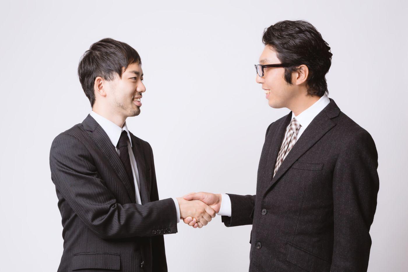 取引が成立して握手を交わすサラリーマンの写真
