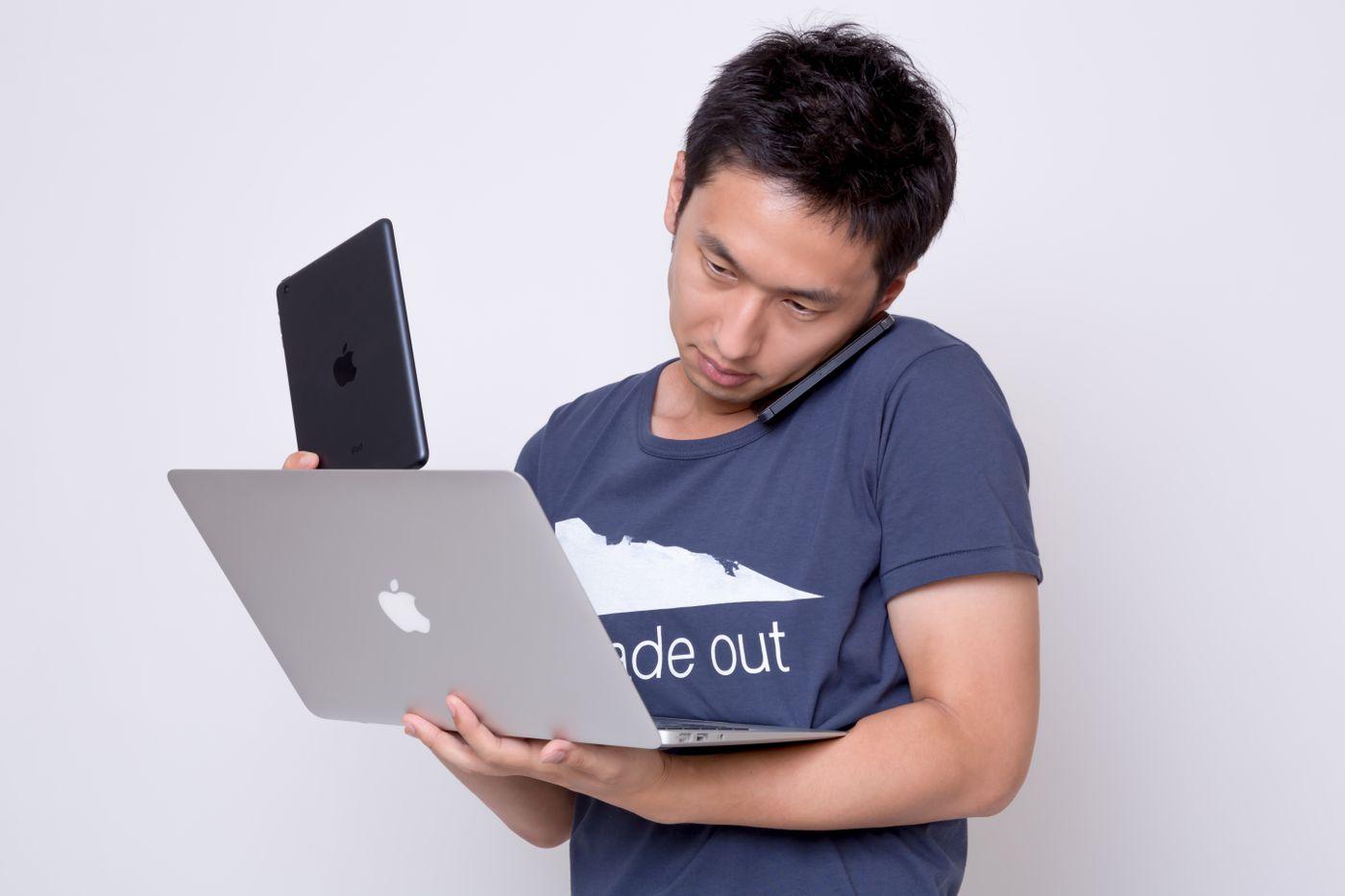 iPhoneとスマホとMBAを使う男性の写真