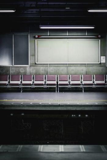 不気味な駅のベンチとホームの写真