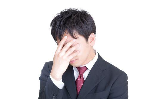 頭を抱えてひどく落ち込む男性の写真
