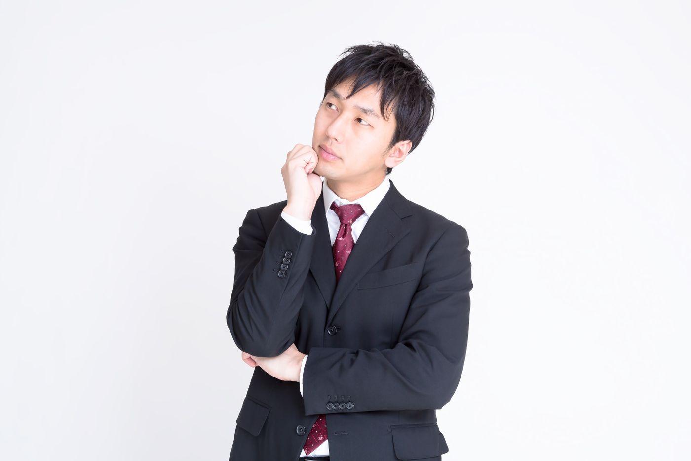 考えるスーツ姿の男性の写真