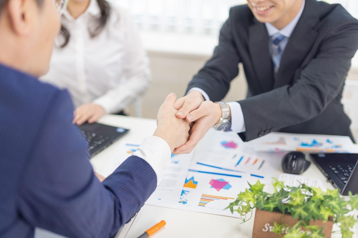 両手でクライアントの手を握りしめる担当者の写真
