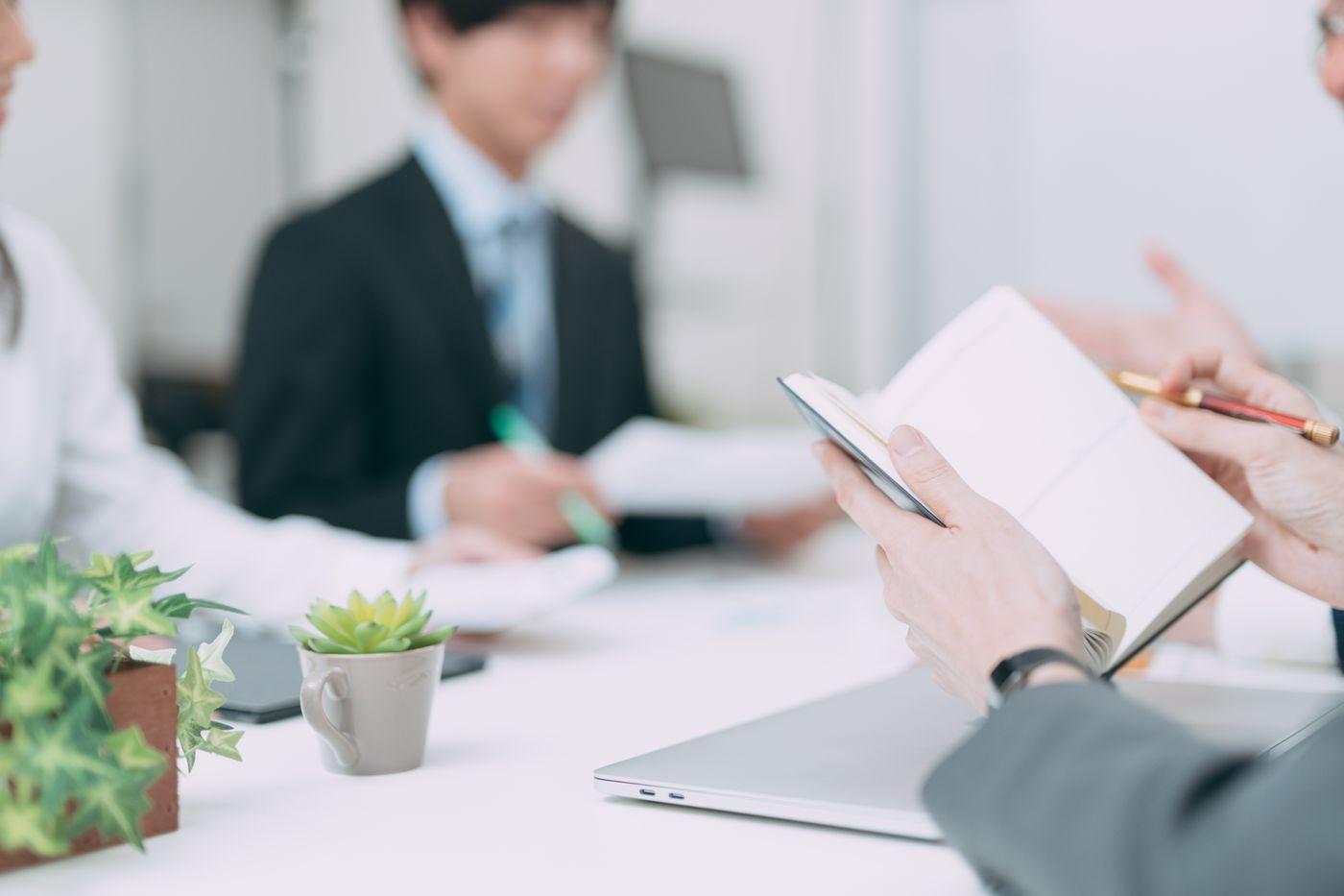 会議中にメモを開いて確認するビジネスマンの写真