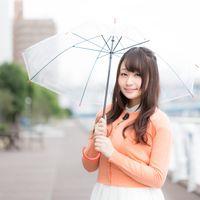 雨の様子を傘をさして伝える美人キャスターの写真