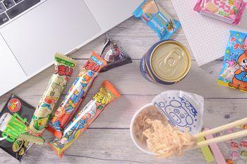食べかけのブタメンと散らばったお菓子の写真