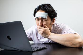 PCの前で吐き気を感じる働き過ぎの男性の写真