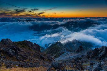 夕焼けに彩られた西鎌尾根と雲海の写真
