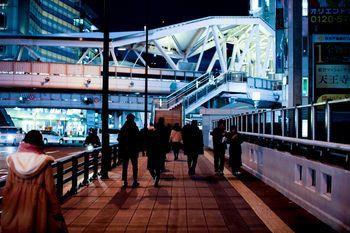 夜の歩道を行き交う人の写真
