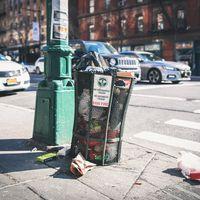 ニューヨークの街角のゴミ箱と散乱するゴミの写真