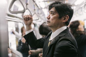 単身赴任で満員電車に揺られて通勤するお父さんの写真