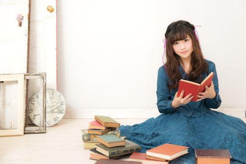 本に囲まれるふんわり女子の写真