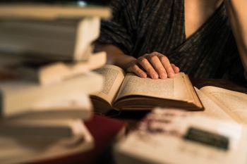 積まれた本と、徹夜で調べものをする様子の写真