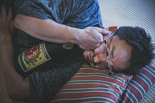 日本酒の一升瓶を抱えて寝落ちする外国人の写真