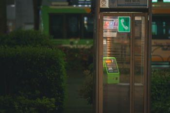 雨に濡れる電話ボックスの写真